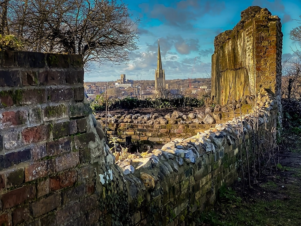 view of the cathedral through the ruins of St. Michael's church in Norwich