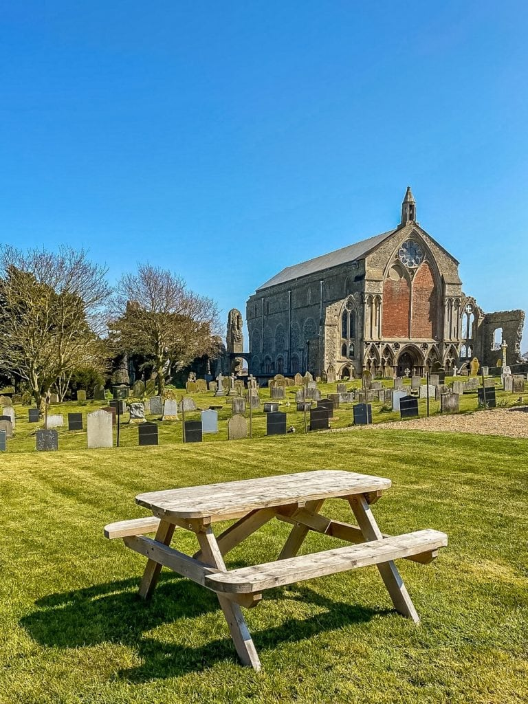 picnic table with binham priory church in the background