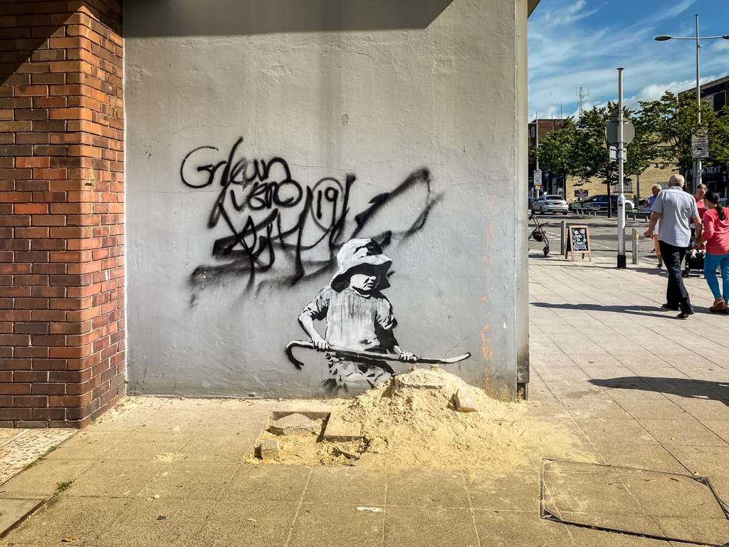 girl with sand on london road in lowestoft by banksy
