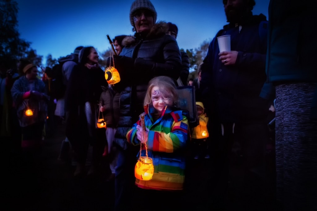 family holding lanterns for the parade at Real Hallloween